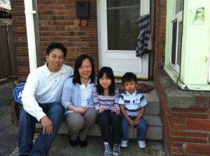 Asian family sitting on steps of family home
