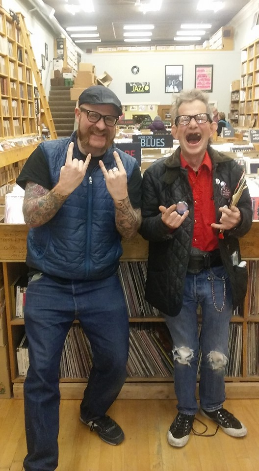 """Two men in the community showing the """"Rock On"""" hand signal."""