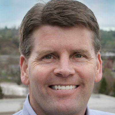 Headshot of man in blue shirt smiling